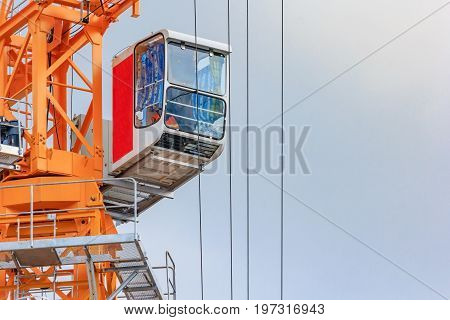 Yellow Tower crane cabin. The cockpit of a construction crane in the cloudy sky background