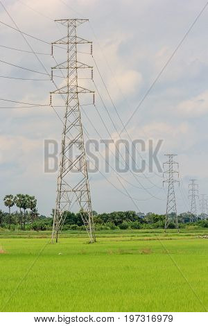 High voltage post or High voltage tower in an agricultural landscape in the Thailand. In the background are the outbuildings of a farm.