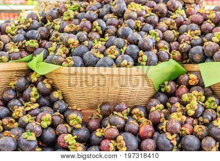Fresh mangosteen queen of fruits (Garcinia mangostana Linn) in the basket at supermarket healthy purple mangosteen fruit food