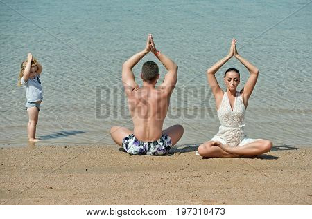 yoga family of man woman and kid young people travel at summer nature on ocean background energy and health youth and love fitness and zen