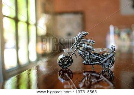Steel chopper motorbike model with blur indoor background.