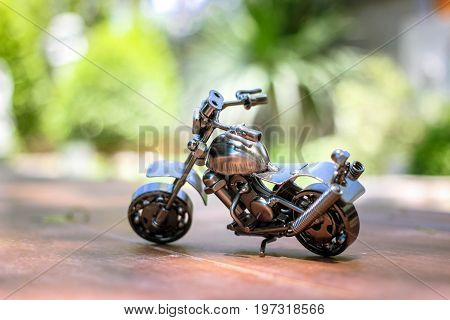 Steel chopper motorbike model with blur outdoor background.