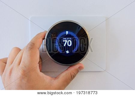 hand adjusting air conditioner button at 70 degree Fahrenheit in the apartment for comfortable