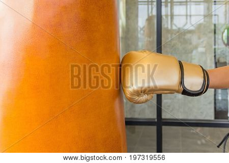 Close-up women hand of boxer at the moment of impact on punching bag in gym