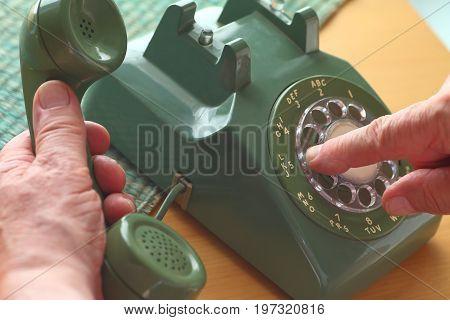 An older man dials a number on a vintage landline phone.