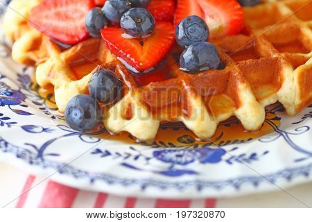 Breakfast waffle with fresh blueberries strawberries and maple syrup on a decorative plate