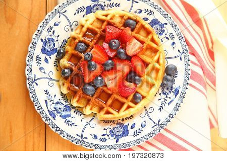 Homemade waffle with fresh blueberries strawberries and maple syrup