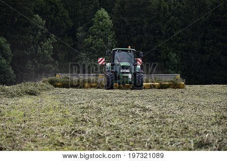 Tractor summarizes dry clover. Farming production season.