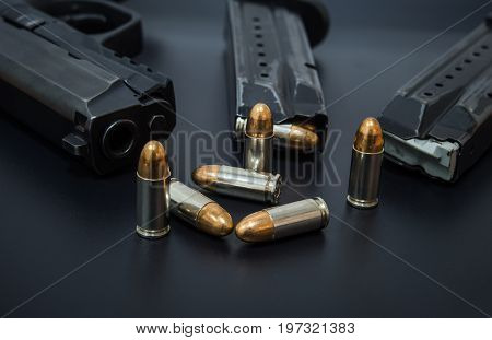 9 mm Pistol, bullets and magazine on drak background. Gun isolated