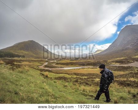 GLENCOE, SCOTLAND - MAY 18 2017 : Man is hiking through the rain in Glencoe, Scotland - UK