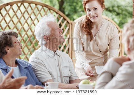 Friendly nurse meets in the garden with her patients from nursing home