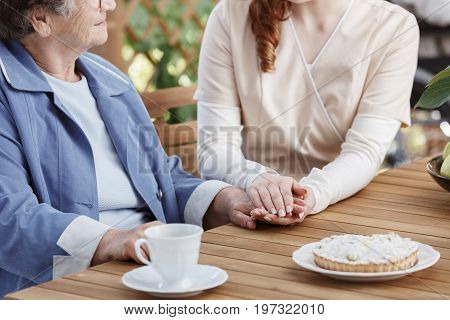 Caregiver Holds The Hand Of Elderly Woman