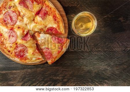 An overhead photo of a pepperoni pizza with a slice cut off, with a glass of white wine, shot from above on a dark rustic texture with a place for text