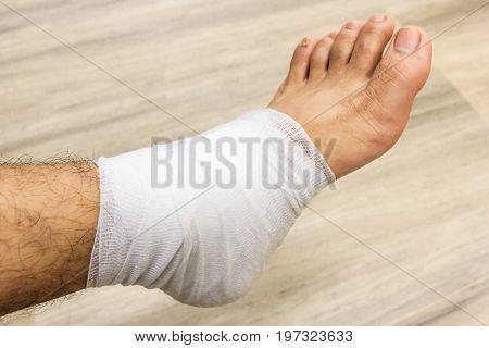 Injured young guy with bandage on patient's leg in clinic closeup