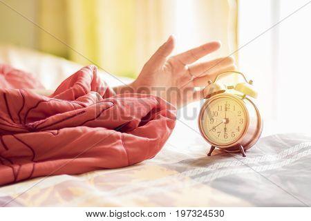 hand stop alarm clock on bed at 6 o'clock