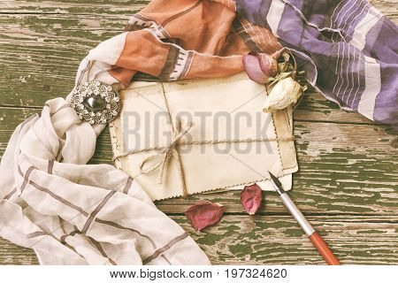 Vintage background with antique brooch pack of greeting cards tied with rope feathers and scarf on wooden table toned image