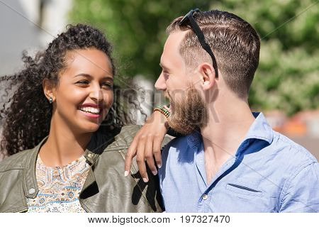 Young Multiracial Couple Looking At Each Other Tenderly