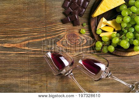Two glasses of red wine, cheese, green grapes and chocolate, top view. Copy space. Still life. Flat lay
