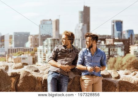 Young Caucasian Buddies Looking Into Distance At City Skyline