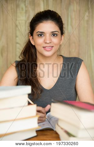 Portrait of happy young Caucasian female student sitting at desk with textbook, looking at camera and smiling