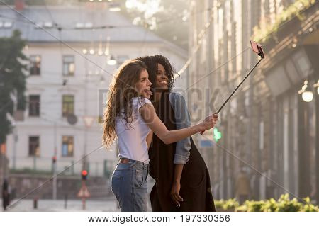 Two young and attractive girls making selfie on the beckground of beautiful city. One girl is black.