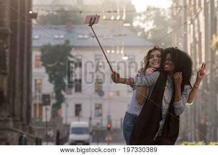 Two happy and attractive women making selfie on the street. One woman is black.