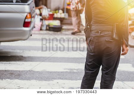 Thailand city officer security on duty in official clothes with radio looking people cross the road and manage traffic.