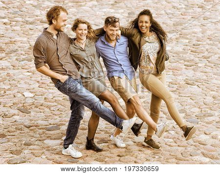 Group of smiling young multiracial friends trying to raise and move their legs simultaneously as fun togetherness activity concept