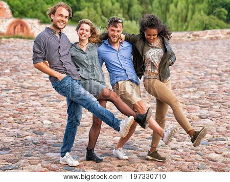 Group Of Smiling Young Friends Raise And Move Legs