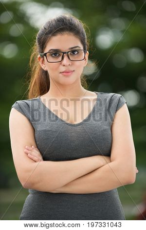 Portrait of positive young Caucasian businesswoman or student wearing grey dress and eyeglasses standing with crossed arms, looking at camera and smiling outdoors