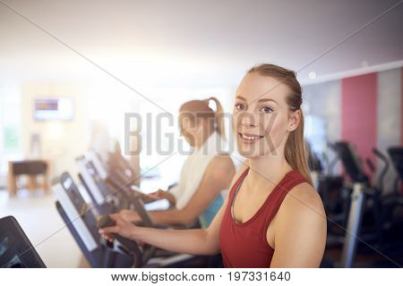 Attractive young woman standing on treadmill in the gym looking at camera and smiling with copy space