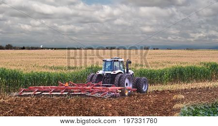 A farmer uses a disc harrow to roll corn stubble back into the soil for nutrients for next season.