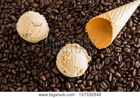 Two scoops of homemade coffee ice cream and an empty ice cream cone on whole dark roasted coffee beans.