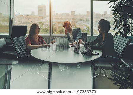 Meeting of three businesspeople in luxury office room near window: group of three co-workers of different races are sitting at oval table and laughing at something strong reflection in the bottom