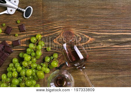 Two glasses of red wine, green grapes and chocolate, top view. Copy space. Still life. Flat lay