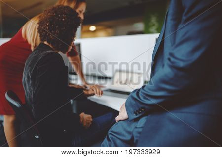 View of male hand of businessman in blue formal suit in office settings with two of his colleagues in defocused background working on laptop with graph on screen shallow depth of field