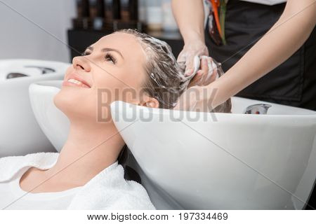 Young female sitting in hair salon hairdo styling washing hair poster