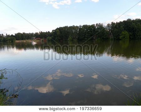 The lakeside view. Clouds reflected in the lake. Summer lake.