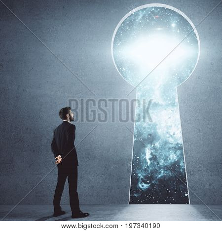 Young businessman in concrete room looking through keyhole opening with space view. Success and future concept. 3D Rendering