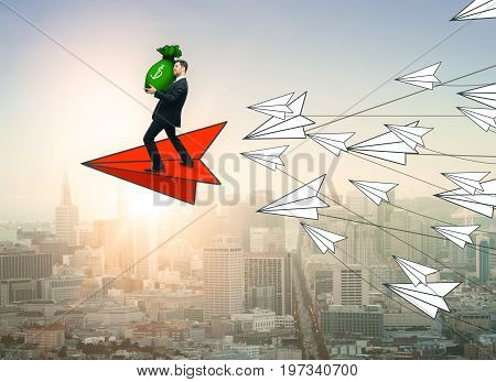 Abstract image of young businessman with money bag flying on red paper plane leading white ones on city background. Leadership and income concept. 3D Rendering
