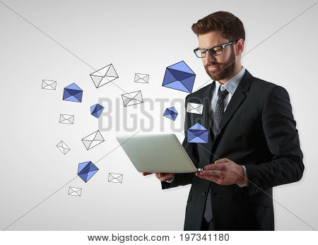 Businessman using laptop with e-mail letters on gray background. Email communication concept