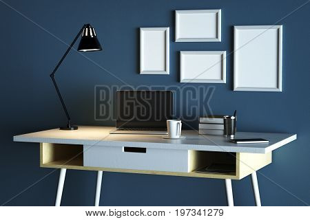 Close up of creative designer desktop with blank laptop coffee cup lamp picture frames and other items on concrete wall background. Mock up 3D Rendering