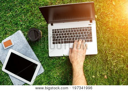 Close-up shot of handsome man's hands touching laptop computer's screen. Businessman using a laptop computer and sitting on the ground.. Sun flare