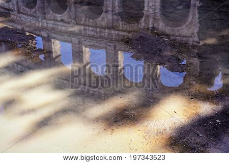 Colosseum reflection in puddle of water after rain Rome Italy