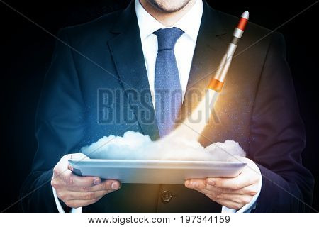 Businessman holding tablet with abstract launching rocket ship in space. Double exposure. Entrepreneurship concept