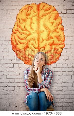 Thoughtful young european woman on brick wall background with creative brain sketch. Brainstorming concept