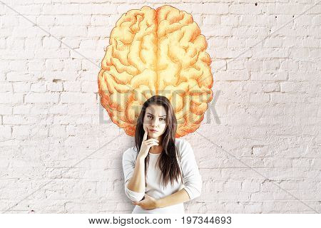 Thoughtful young european businesswoman on brick wall background with creative brain sketch. Intelligence concept