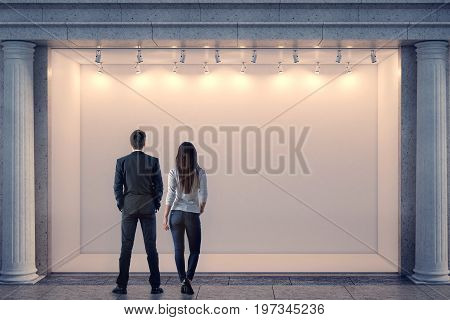 Back view of man and woman looking at illuminated clear storefront and columns in night city. Advertisement and commerce concept. Mock up 3D Rendering