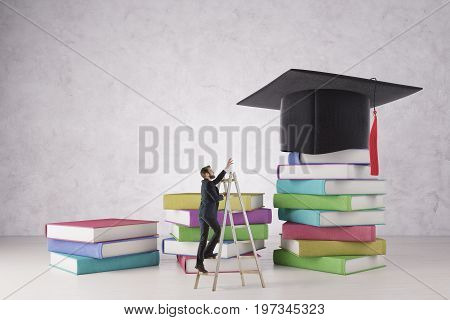 Businessman on ladder trying to reach mortarboard placed on abstract colorful book ladder on concrete background. Education and hard work concept. 3D Rendering