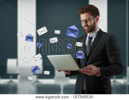 Businessman using laptop with e-mail letters in blurry interior. Email newsletter concept. 3D Rendering